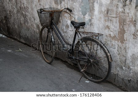 Old rustic bicycle on the wall  - stock photo