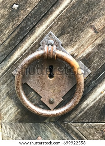 Old Rustic Door Knocker Made Of Iron And Hanging On Wooden Surface.
