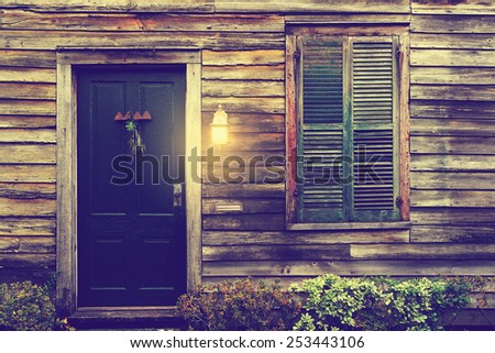 Old rustic vintage antique dilapidated house home building structure cottage with green intricate front door and window with shutters closed shut and porch light lantern glowing turned on - stock photo