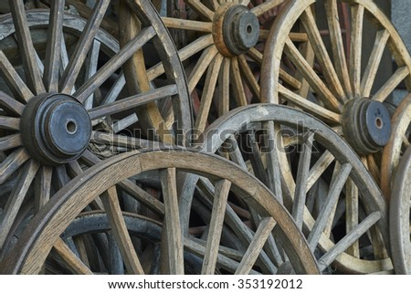 Old rustic wagon wheels stacked over each other  - stock photo