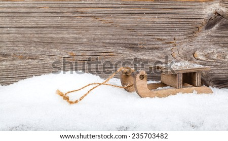 old rustic wooden sledge, over snow, wooden background - stock photo