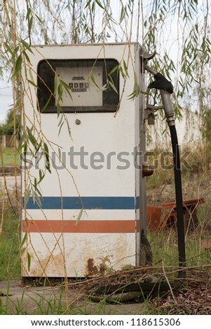 Old, rusty and abandoned gas pump against nature - stock photo