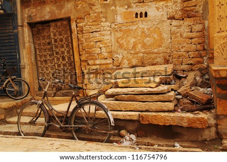 Old rusty bicycle leaning against a wall in the city in India