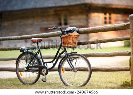 Old rusty bicycle with basket in countryside - stock photo
