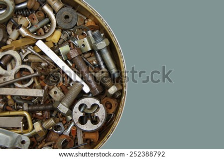 Old rusty bolts, screws, nuts, screws, brackets, various metal details in round iron container on a gray background - stock photo
