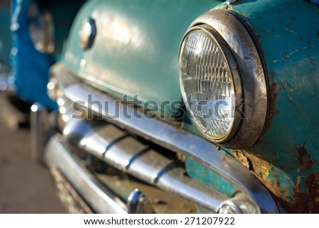 old rusty car's headlight and bumper side view - stock photo