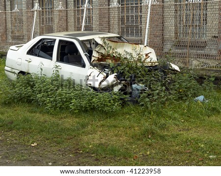 old rusty car wreck integrating itself into nature - stock photo