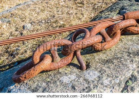 Old rusty chain and wire set in the rock to anchor heavy equipment.
