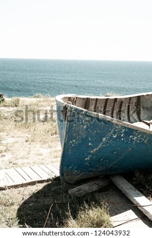 Old rusty classic vintage wood boat on the beach. Sea travel and fishing concept - stock photo
