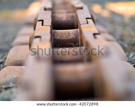 Old Rusty Continuous Tracks on Gravelly Ground - stock photo