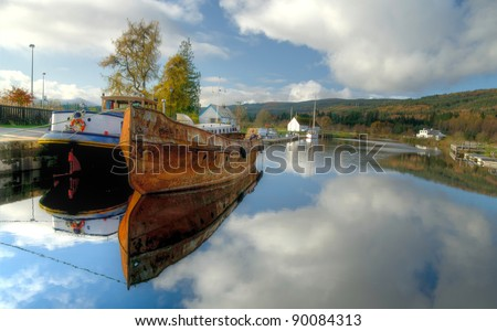 Old rusty fishing boat anchored on Caledonian channel in Scotland - stock photo