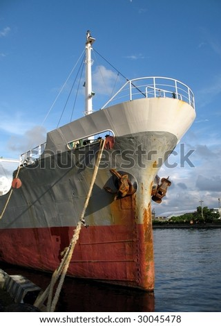 Old rusty freight carrying ship anchored in port - stock photo