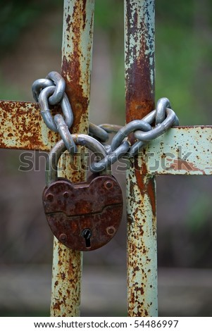 Old rusty gates closed with chain and  padlock - stock photo