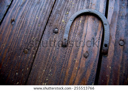 Old rusty horseshoe pinned to a wall of brown wooden boards - stock photo