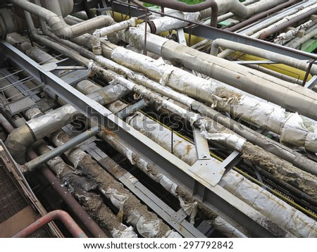 Old rusty industrial steel pipelines, valves and equipment at power plant. - stock photo