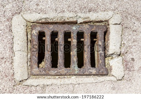Old rusty iron sewer cover on one of the streets on the Cote d'Azure - stock photo