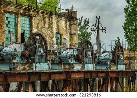 old rusty lock mechanism at an abandoned dam - stock photo