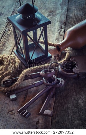 Old rusty lock with keys, vintage lamp, bottle from clay and rope on wooden board. Retro stylized photo. - stock photo