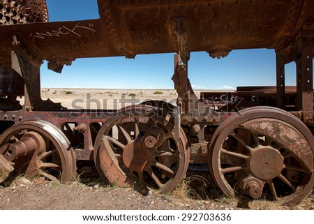 Old rusty locomotive with wheels in the close up .Uyuni, train cemetery, Bolivia. Blue sky background - stock photo