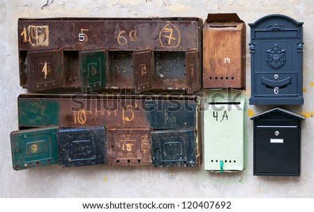 Old rusty mailboxes on the wall - stock photo