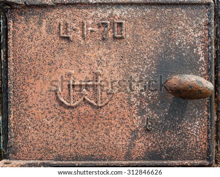 Old rusty metal furnace door with the room and anchors. - stock photo