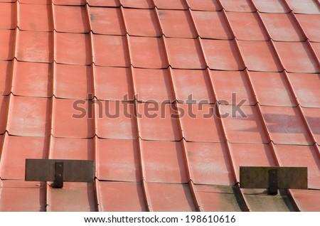 Old rusty metal orange roof on villa. - stock photo
