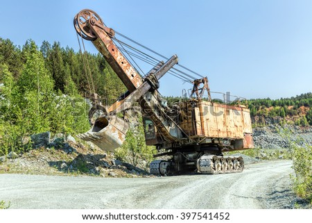 Old rusty mine excavator in a stone quarry