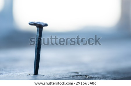Old rusty nail in the wooden plank over the opened window - stock photo
