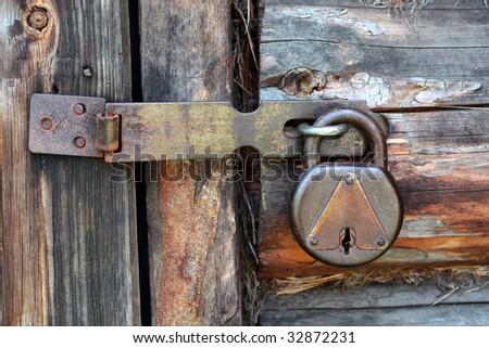 Old rusty padlock on a closed door - stock photo