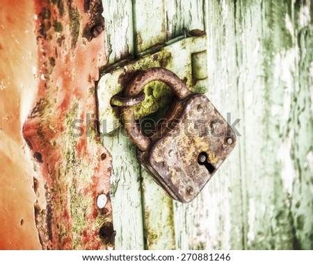 old rusty padlock on old wooden door - stock photo
