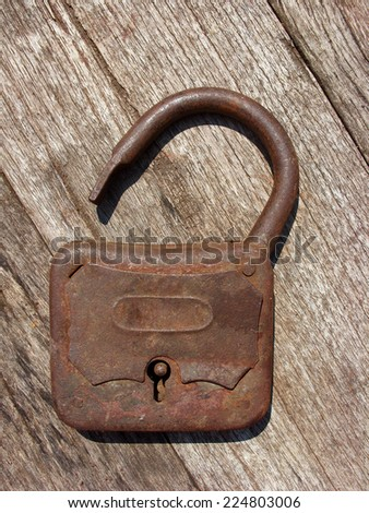 Old rusty padlock on wooden background