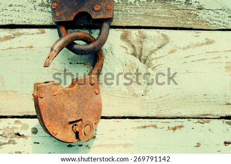 Old rusty padlock on wooden background - stock photo
