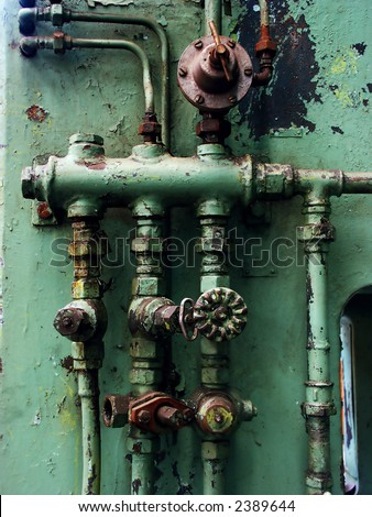 Old rusty pipes and valves with water leaks - stock photo