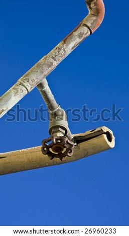 Old rusty plumbing pipes and a valve with cracked insulation - stock photo