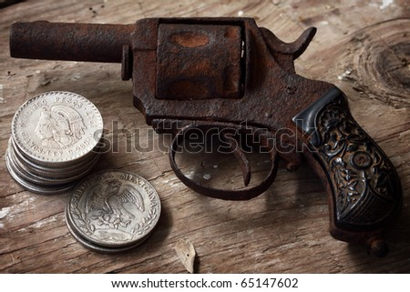 Old rusty revolver pistol and mexican coins - stock photo