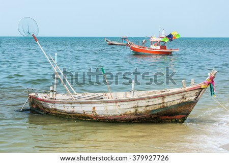 Old rusty rowboat for fishing parking near the beach - stock photo