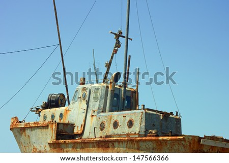 Old rusty small ship against a cloudless sky - stock photo