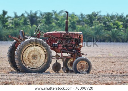 Old rusty tractor sitting in a field to do the work even after all those years - stock photo