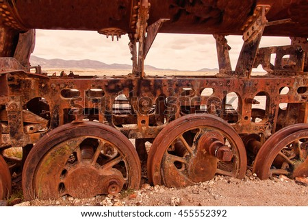 Old rusty train covered with sand wheels in the cemetery of old trains in Uyuni, Bolivia