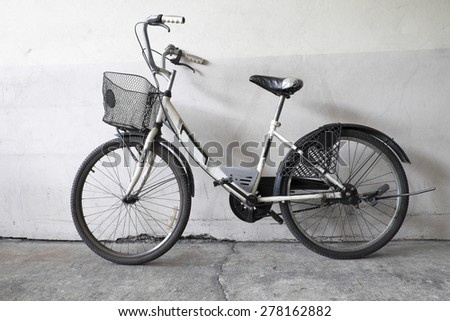 Old rusty vintage bicycle near the concrete wall still life - stock photo