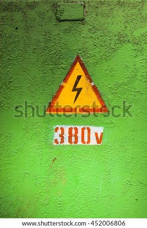 Old rusty warning high voltage sign on cracked green metal surface with numbers three eight zero - stock photo