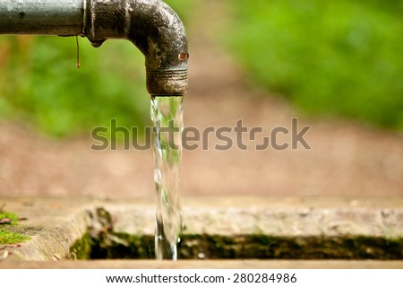 Old rusty water tap with flowing water and grunge fountain in the forest. Selective focus, only main part of fountain is in the focus. - stock photo