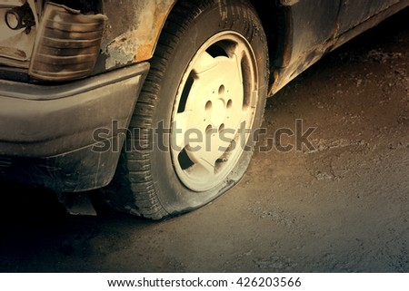 Old rusty wrecked car with a punctured tire. Toned - stock photo