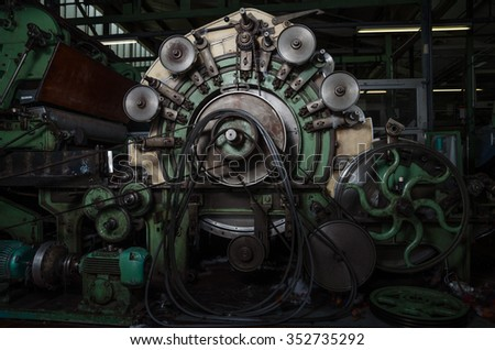 Old 1960s industrial cotton working machine in a dark factory atmosphere - stock photo