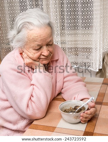 Old sad woman eating at home - stock photo