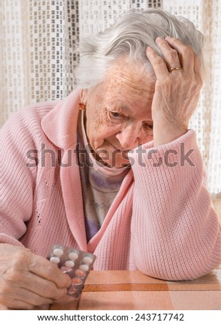 Old sad woman holding pills at home - stock photo