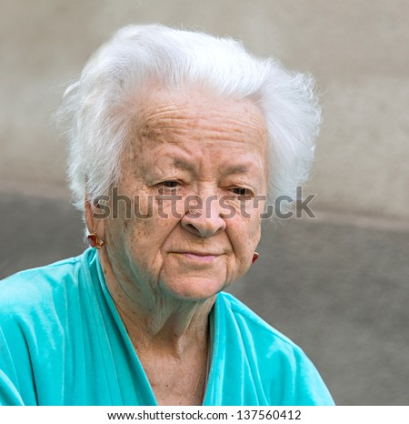 Old sad woman on a gray background