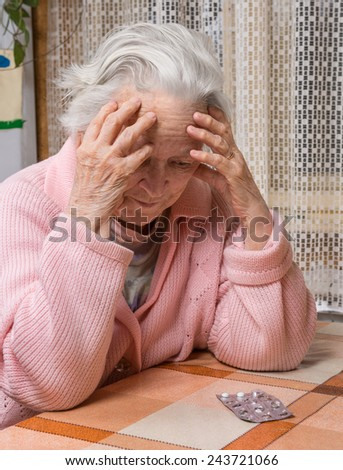 Old sad woman with pills at home.  Worried about  having to take too many pills - stock photo