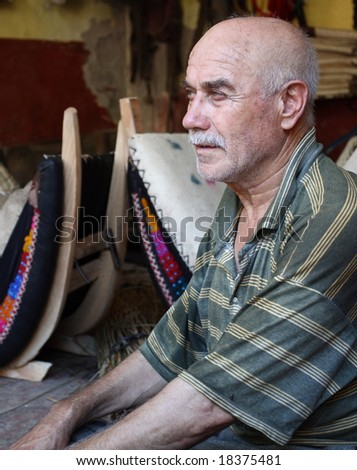 old saddle maker sitting in front of his products - stock photo