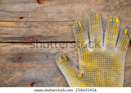 Old safety gloves on wooden background, Gloves on dirty works. - stock photo